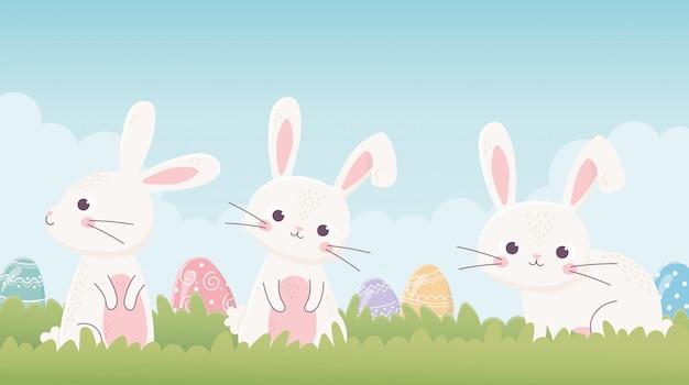 Felices pascuas lindos conejitos con huevos en la hierba