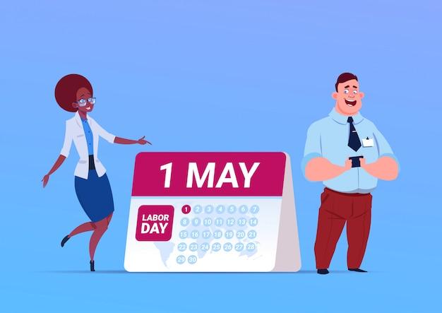Feliz 1 de mayo día del trabajo cartel con hombre de negocios y mujer sobre calendario