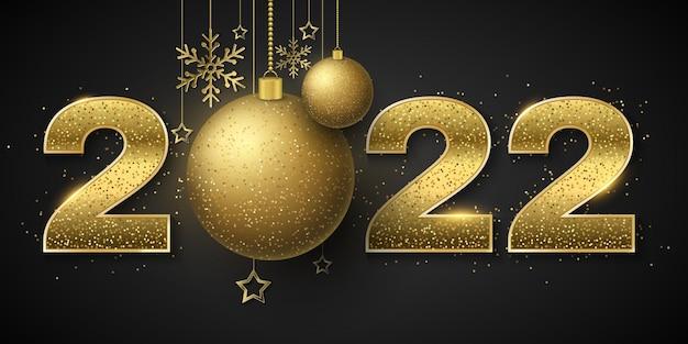 Feliz año nuevo 2022. números dorados brillantes con lentejuelas y adornos navideños de bolas colgantes, estrellas y copos de nieve.