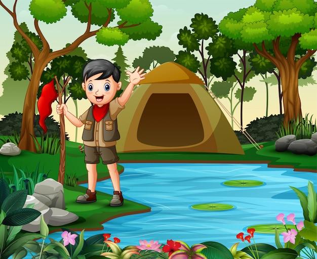 Feliz boy scout acampando en la naturaleza