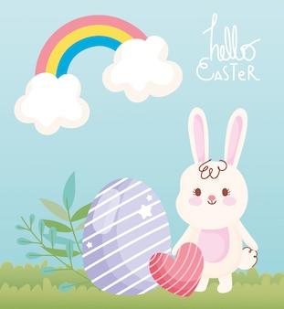 Feliz conejo blanco de pascua con decoración de corazón y huevo en hierba arco iris cielo ilustración