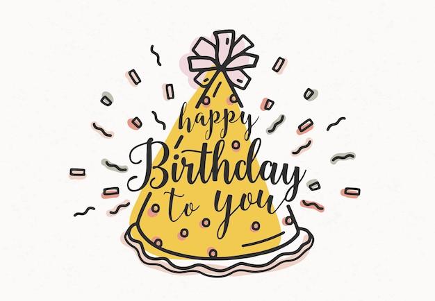 Feliz cumpleaños a ti, escrito a mano con letra cursiva y decorado con gorro de fiesta de cono y confeti