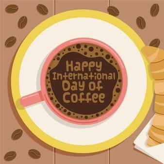 Feliz día internacional del café en taza con croissant