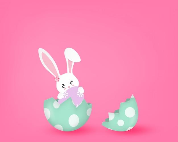Feliz día con lindo conejito en un huevo medio roto en rosa