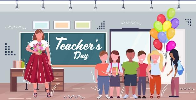 Feliz día del maestro concepto de celebración navideña maestro con niños de escuela de raza mixta sosteniendo globos de aire parados juntos cerca del interior del aula de pizarra