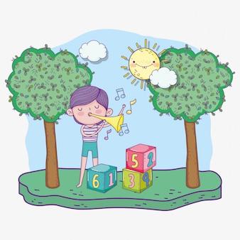 Feliz día de los niños, niño jugando con trompeta musical en el parque