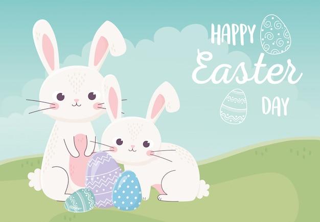Feliz día de pascua, conejos y huevos decorativos hierba naturaleza