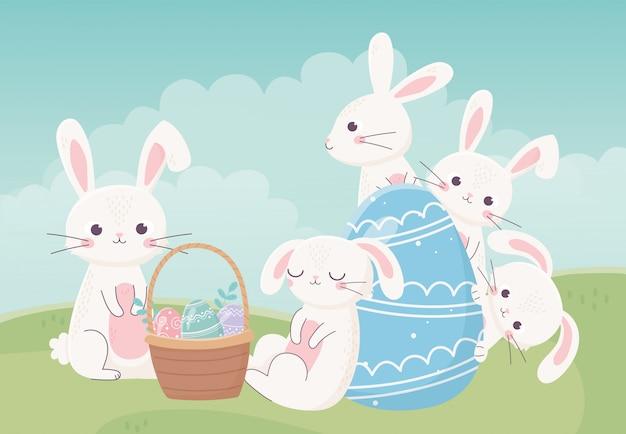 Feliz día de pascua, huevos de canasta de conejos blancos en pasto