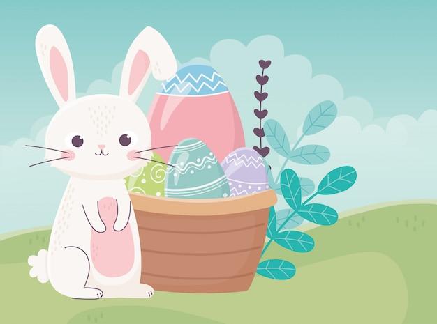 Feliz día de pascua, huevos de conejo lindo en la naturaleza del follaje de la cesta