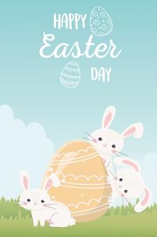 Feliz día de pascua, lindos conejos con huevo pintado en decoración de hierba