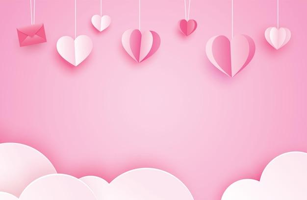 Feliz día de san valentín tarjetas de felicitación con corazones de papel colgando sobre fondo rosa pastel.