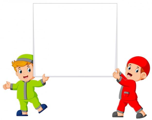 Feliz dos muchacho musulmán con gran cartel en blanco