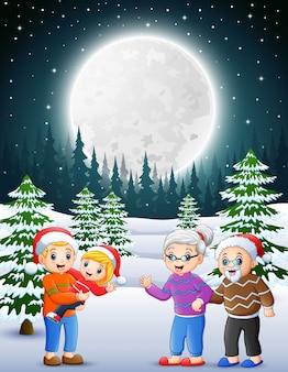 Feliz familia en el jardín nevado por la noche