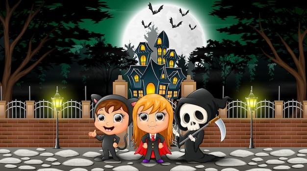 Feliz grupo de halloween celebra frente a casa embrujada