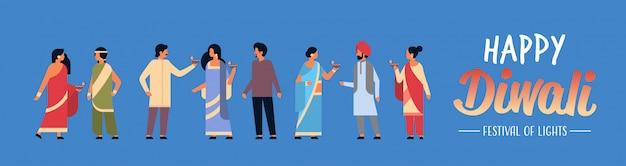 Feliz grupo de personas indias diwali vistiendo ropas tradicionales nacionales sosteniendo la bandera de la lámpara de aceite