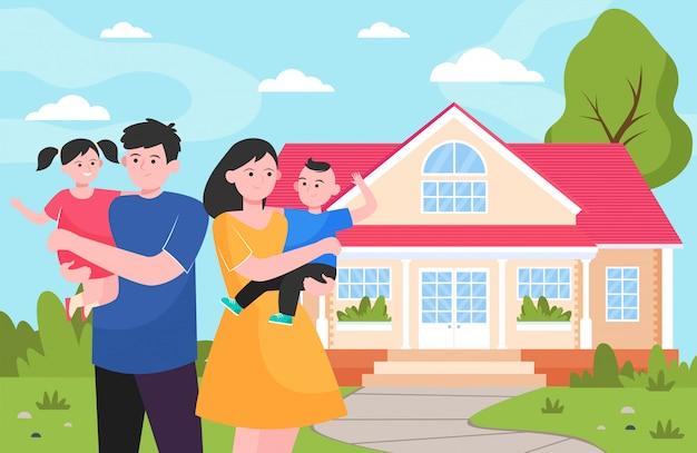 Feliz joven familia de pie delante de la casa