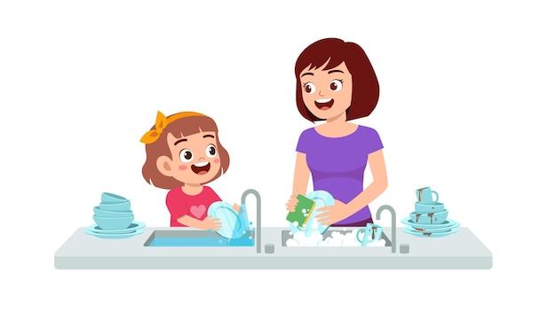 Feliz linda niña lavando el plato con la madre