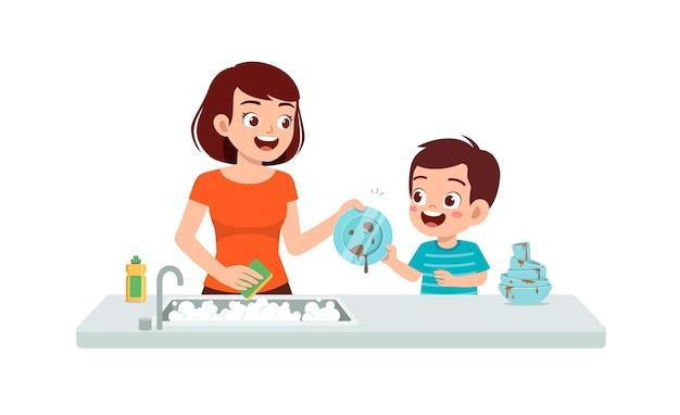 Feliz lindo niño lavando un plato con la madre