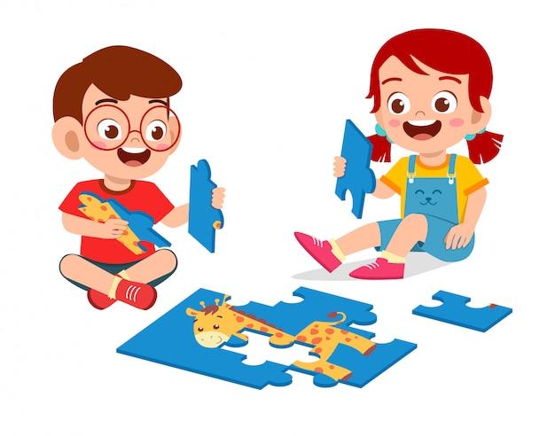 Feliz lindo niño niño y niña juegan rompecabezas