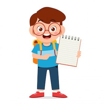 Feliz lindo niño niño sostenga cuaderno y lápiz