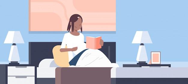 Feliz mujer leyendo libro niña sentada en la cama dormitorio moderno interior embarazo y maternidad