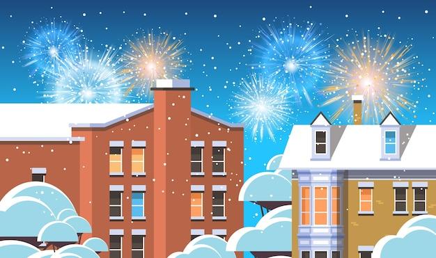 Feliz navidad feliz año nuevo cartel festivo colorido saludo de fuegos artificiales sobre invierno casas de la ciudad ciudad nevada calle tarjeta de felicitación ilustración vectorial horizontal plana
