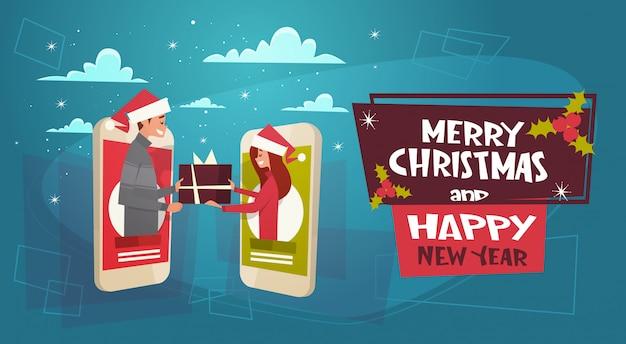 Feliz navidad y feliz año nuevo cartel con pareja dando caja de regalo a través de la pantalla del teléfono celular