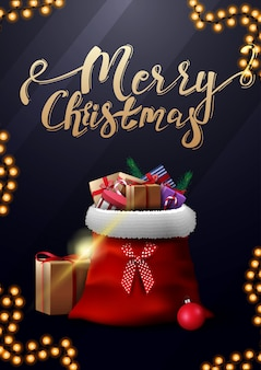 Feliz navidad, postal azul vertical con letras doradas y bolsa de papá noel con regalos