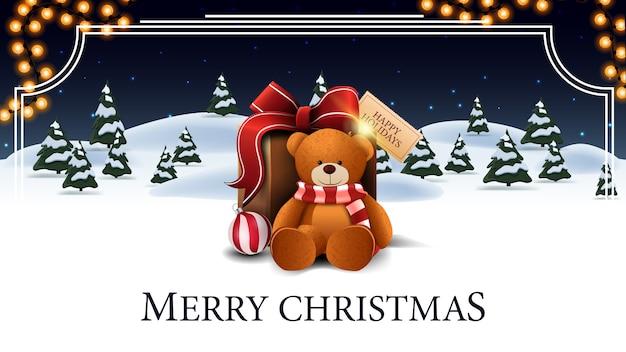 Feliz navidad, postal blanca y azul con bosque de invierno de dibujos animados con abetos, cielo estrellado, guirnalda y presente con oso de peluche