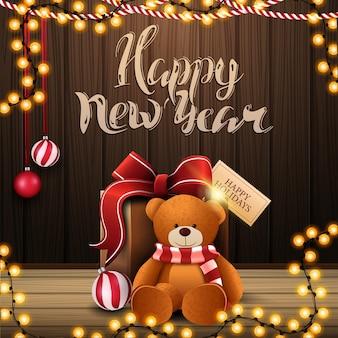 Feliz navidad, postal de felicitación con regalo con osito de peluche, pared de madera y guirnalda