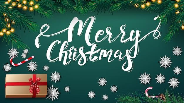 Feliz navidad, postal verde con guirnalda, árbol de navidad, presente, copos de nieve de papel y lata de caramelo, vista superior