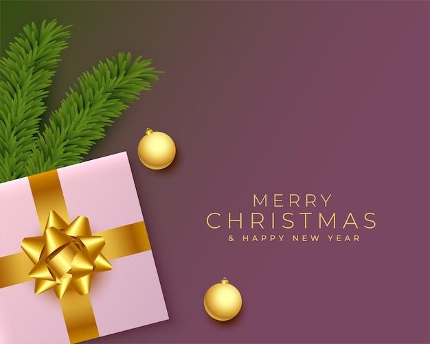 Feliz navidad saludo realista con regalos y hojas de pino.
