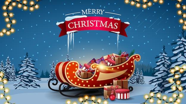 Feliz navidad, tarjeta de felicitación con trineo de santa claus con regalos y paisaje invernal con pinos cubiertos de nieve, cielo azul estrellado y llanuras cubiertas de nieve.