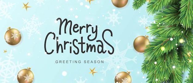 Feliz navidad tarjeta de texto de letras a mano. rama de pino realista con adornos de bolas de oro.