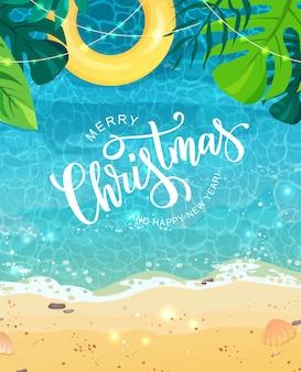 Feliz navidad texto de letras a mano para la exótica celebración del año nuevo. costa de verano con arena y anillo de natación amarillo, hojas tropicales, vista superior.