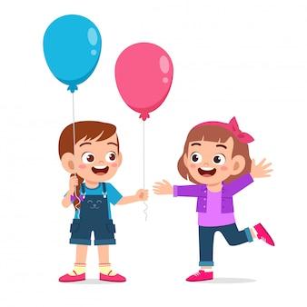 Feliz niña niño lindo dar globo a amigo