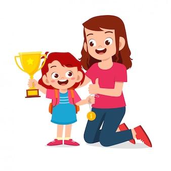 Feliz niña niño lindo llevar trofeo con mamá