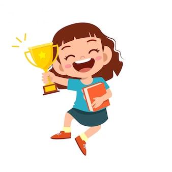 Feliz niño lindo niña ganar juego trofeo de oro