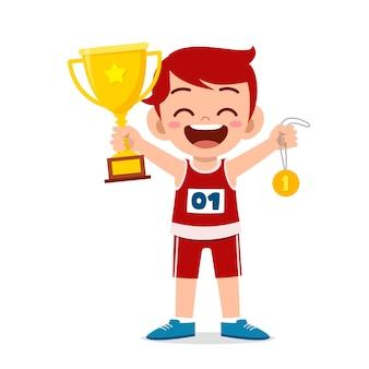 Feliz niño lindo con trofeo y medalla de oro