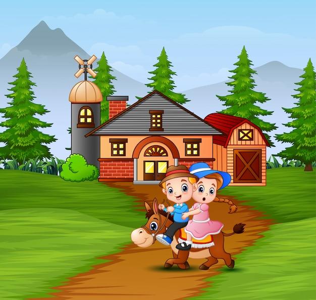 Feliz niño y niña montando un caballo en frente de la granja