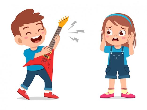 Feliz niño pequeño niño lindo tocar la guitarra para molestar a un amigo