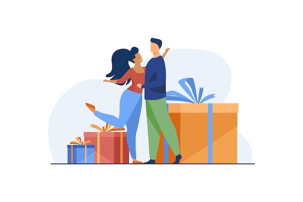 Feliz pareja abrazándose y de pie cerca de regalos.