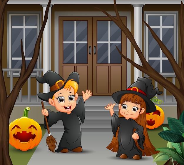 Feliz pareja de brujas de pie frente a la casa