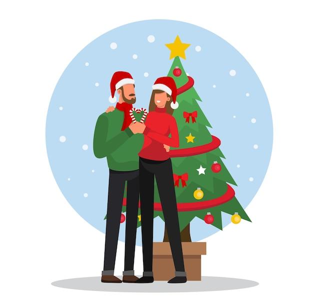 Feliz pareja de enamorados delante del árbol de navidad