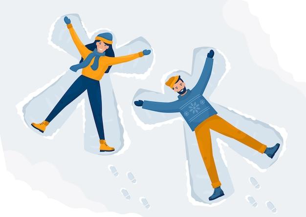 Feliz pareja hace ángeles de nieve. un hombre y una mujer yacen en el suelo.