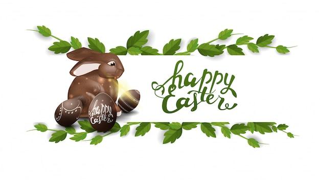 Feliz pascua, postal blanca con marco de liana y chocolate. conejito de pascua.