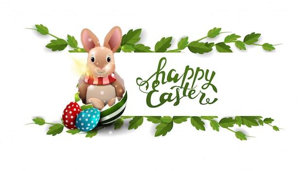 Feliz pascua, postal blanca con marco de liana y conejito de pascua en huevo.