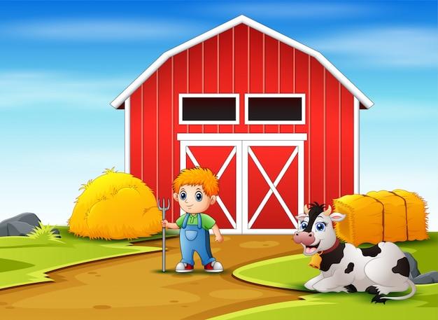 Feliz pequeño agricultor y vaca en la granja