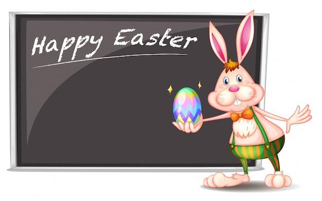 Un feliz saludo de pascua con un conejito al lado de un tablero gris