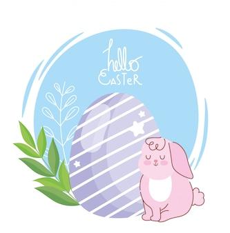 Feliz tarjeta de pascua, conejo rosa sentado con decoración de huevo